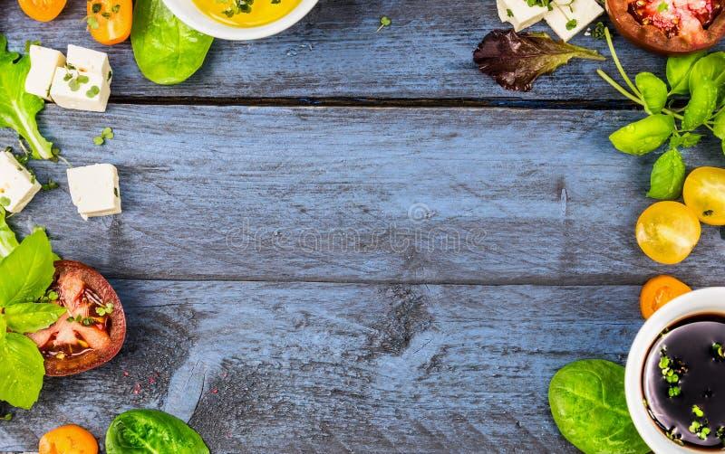 与沙拉成份的食物框架:油、醋、蕃茄、蓬蒿和乳酪在蓝色土气木背景 库存照片