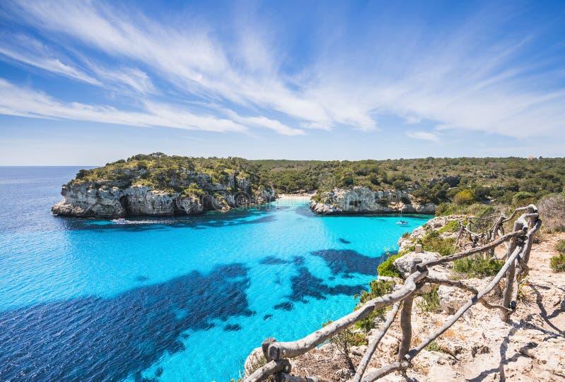 与沙滩和帆船,梅诺卡海岛,西班牙的美丽的海湾 免版税库存图片