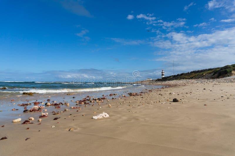 与沙滩和灯塔的海景风景在距离 免版税库存照片