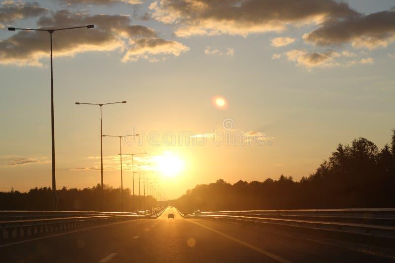 与沥青高速公路路的美好的日落在农村场面 在晚上天空的大云彩 库存照片