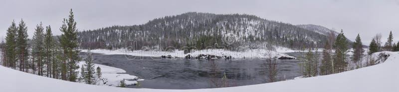 与河和木头的冬天风景包括小山 库存图片