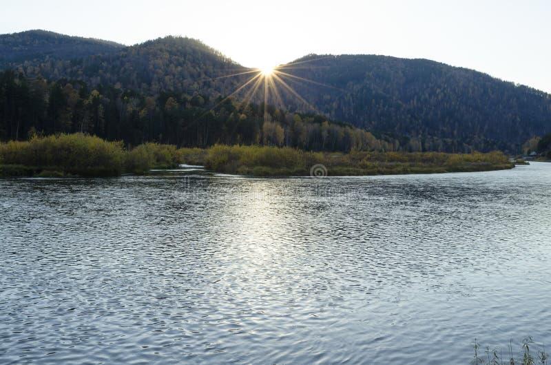 与河和森林的秋天风景沿落日的光芒的银行 库存图片
