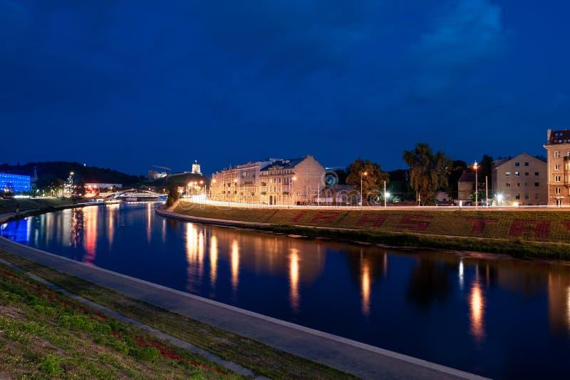 与河涅里斯河和Gediminas城堡的维尔纽斯老镇都市风景在背景中 晚上照片写真 免版税库存照片