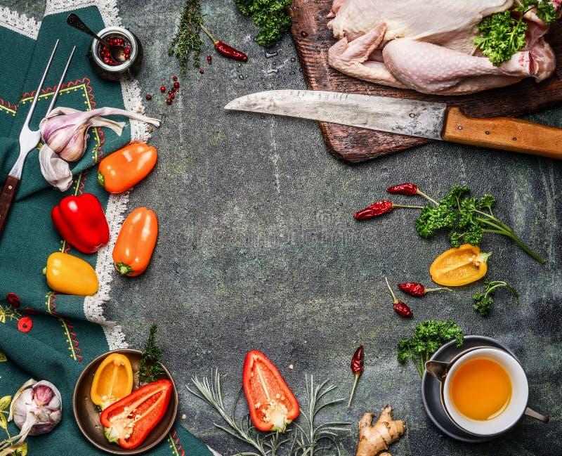 与油和菜成份的未加工的整鸡烹调的在土气背景,框架,顶视图 库存图片