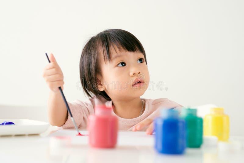与油漆刷和五颜六色的油漆的小的亚洲女孩绘画 库存照片