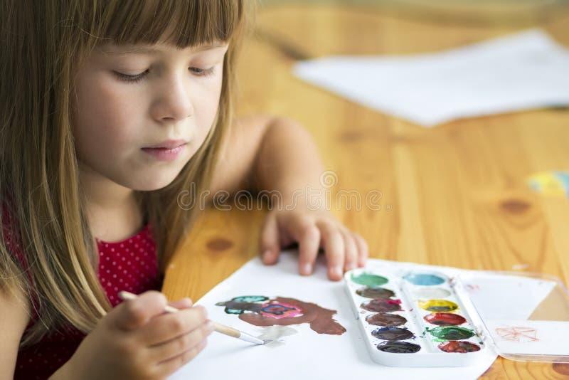 与油漆刷和五颜六色的pai的逗人喜爱的小孩女孩绘画 库存照片