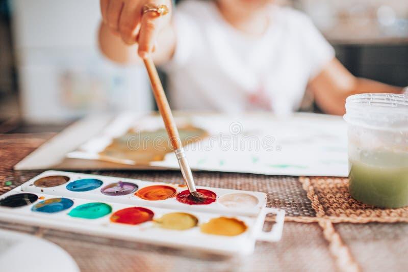 与油漆刷和水彩的美好的白肤金发的女孩绘画在厨房里 孩子活动概念 ?? o 库存照片