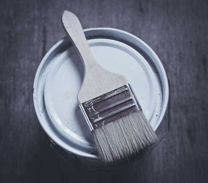 与油漆桶的画笔在木板条 库存图片
