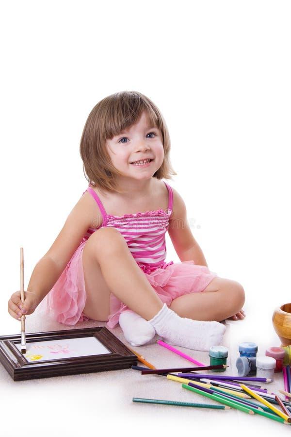 与油漆的微笑的三年的女孩图画 免版税图库摄影