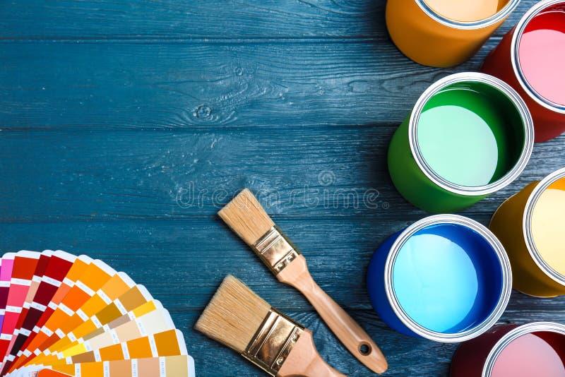 与油漆罐头、刷子和色板显示的平的位置构成在木背景 免版税库存照片