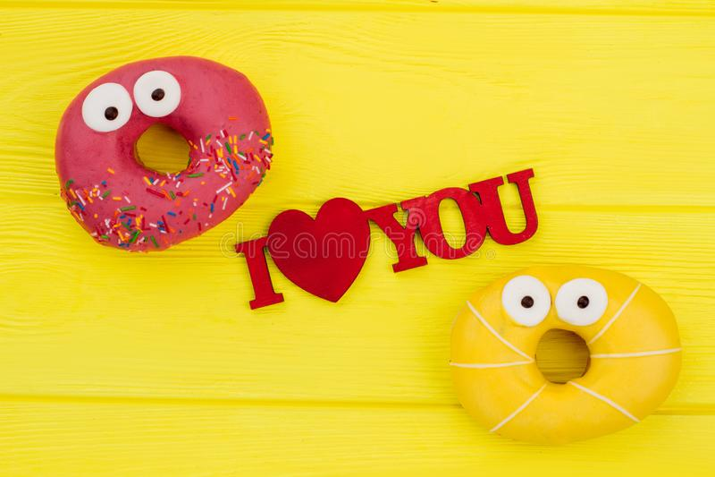 与油炸圈饼的浪漫构成在黄色背景 免版税库存照片