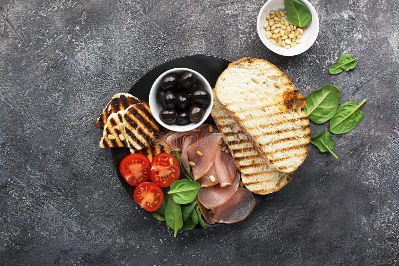 与油煎的乳酪haloumi,橄榄, bruschetta,蕃茄,橄榄,松果,橄榄油,蜂蜜的开胃快餐和 免版税库存照片