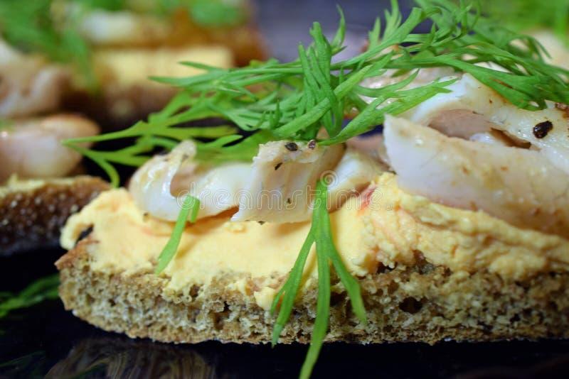 与油煎的栖息处鱼片、辣奶油奶酪和莳萝的三明治 免版税库存图片