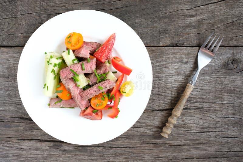 与油煎的牛排、蕃茄、胡椒和香葱的沙拉 库存照片