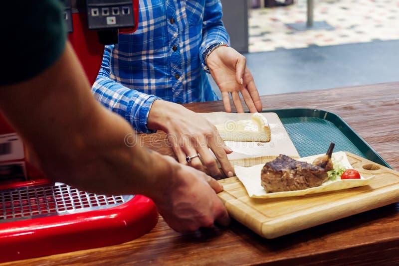 与油煎的菜和乳酪蛋糕的服务的水多的烤牛排 图库摄影
