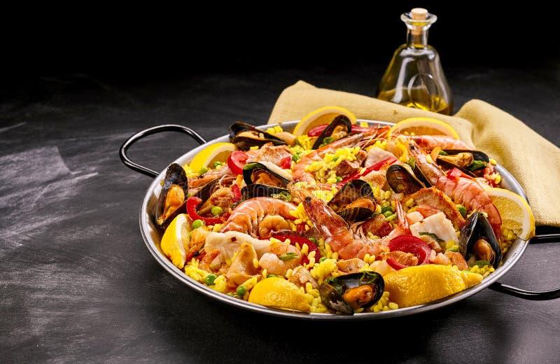 与油的五颜六色的西班牙海鲜肉菜饭盘 免版税库存图片