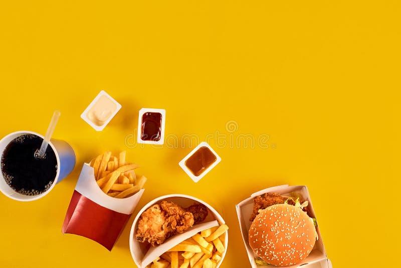 与油腻油煎的餐馆的快餐概念去掉当洋葱圈、汉堡、炸鸡和炸薯条作为a 免版税库存照片