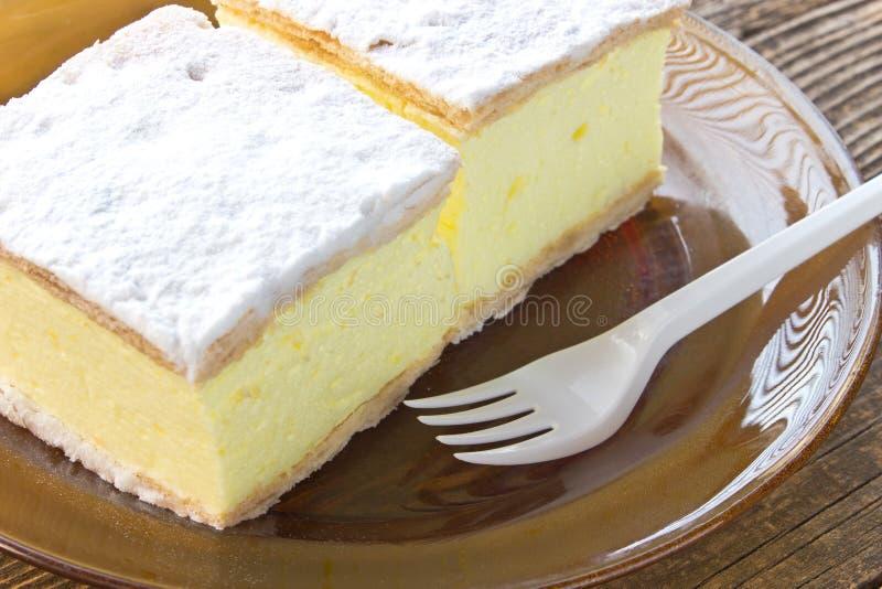 与油酥点心层数的奶油馅饼在板材的在木桌上 免版税图库摄影
