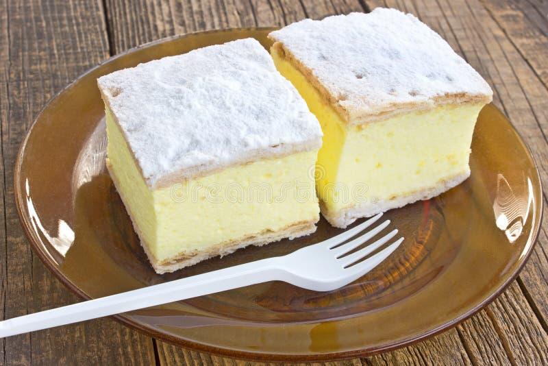 与油酥点心层数的奶油馅饼在板材的在木桌上 库存照片