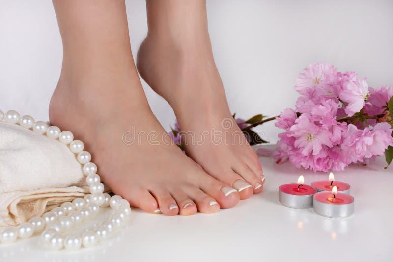 与法国修脚的妇女赤脚在白色毛巾和装饰蜡烛、珍珠和桃红色花在秀丽演播室 免版税库存照片