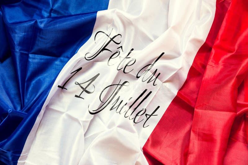 与法国文本,概念国庆节的法国旗子7月14日 免版税库存图片