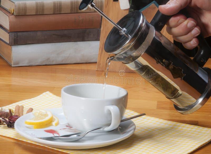 与法国新闻茶壶的倾吐的清凉茶到白色杯子里 免版税图库摄影