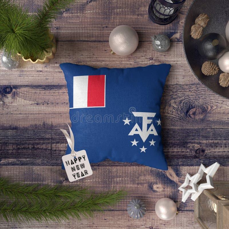 与法属南部领地旗子的新年快乐标记在枕头 在木桌上的圣诞装饰概念与 免版税库存照片