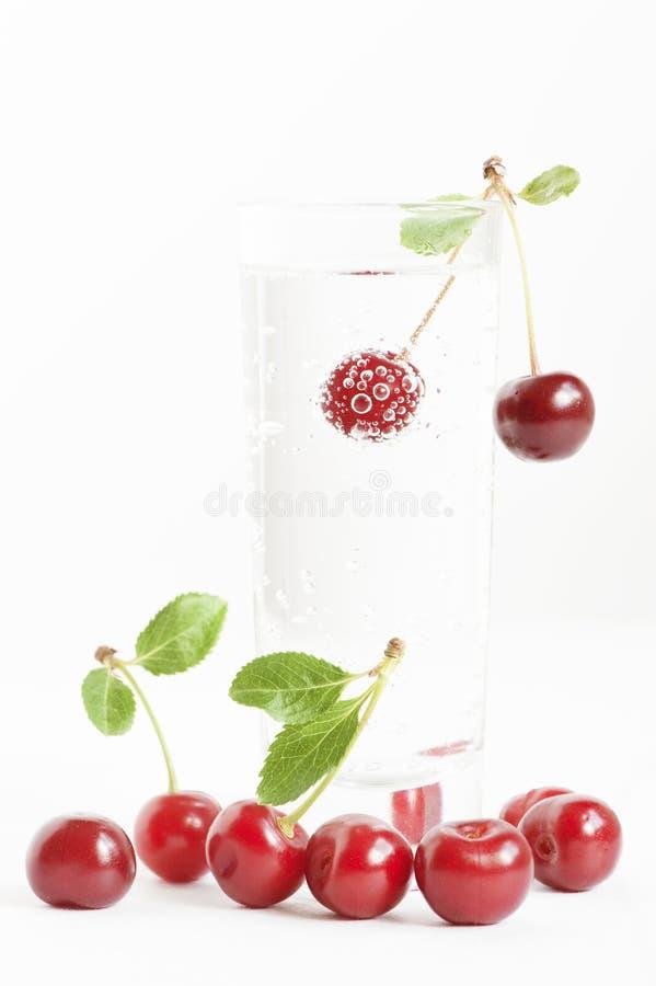 与泡影的樱桃在杯水 库存照片