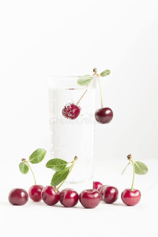 与泡影的樱桃在杯水 免版税图库摄影