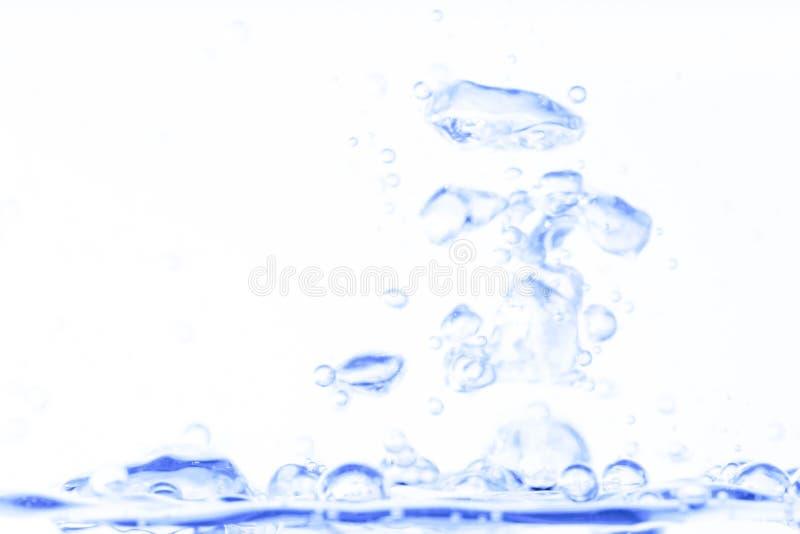 与泡影的蓝色透明水色水飞溅在白色干净的背景摘要 免版税图库摄影