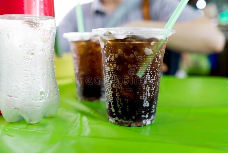与泡影的黑闪耀的可乐水在有stro的塑料杯子 库存图片