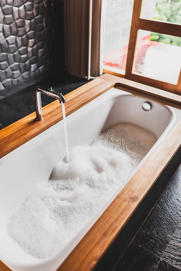 与泡沫泡影的水填装的浴 免版税库存照片