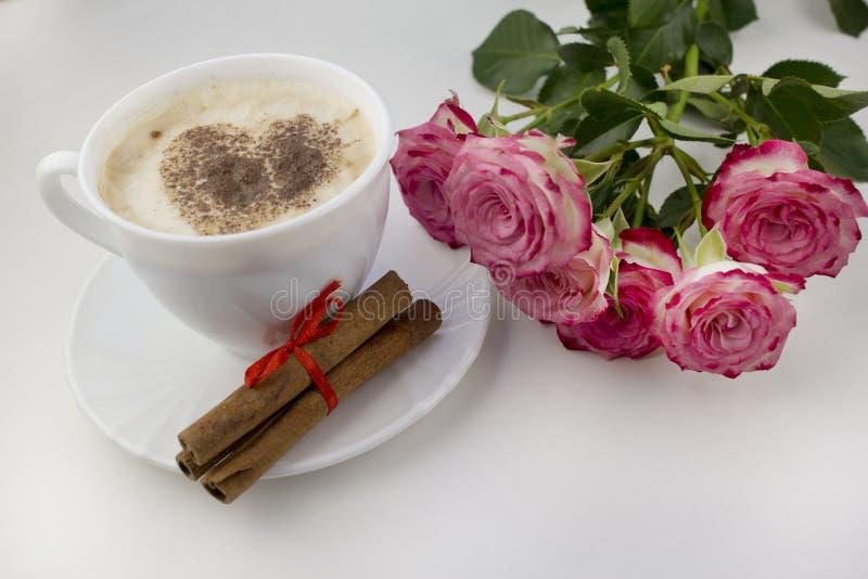 与泡沫的咖啡与桂香的心脏在白色背景的 甜桃红色的玫瑰 图库摄影