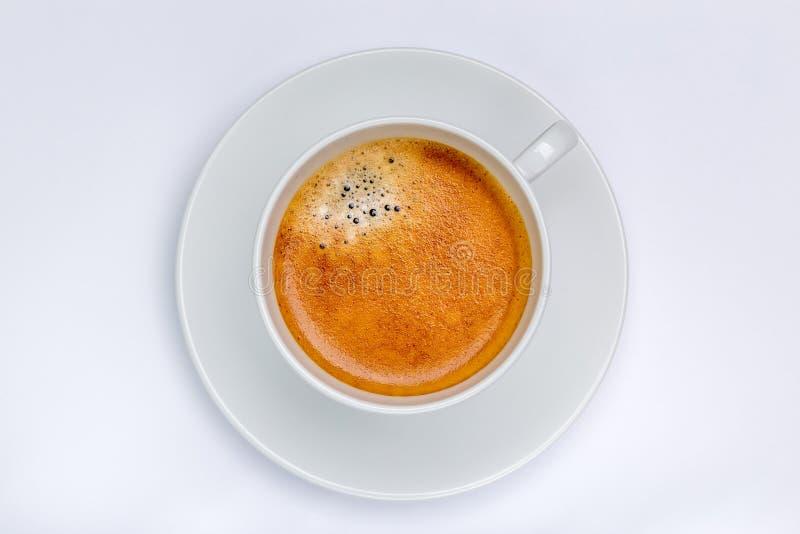 与泡沫的热的无奶咖啡在有白色backg的白色杯子起泡 图库摄影