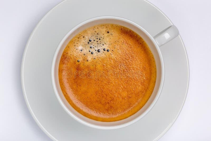 与泡沫的热的无奶咖啡在有白色backg的白色杯子起泡 免版税库存图片
