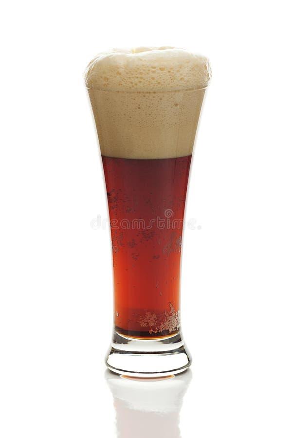 与泡沫的黑啤酒在一块高玻璃 免版税图库摄影