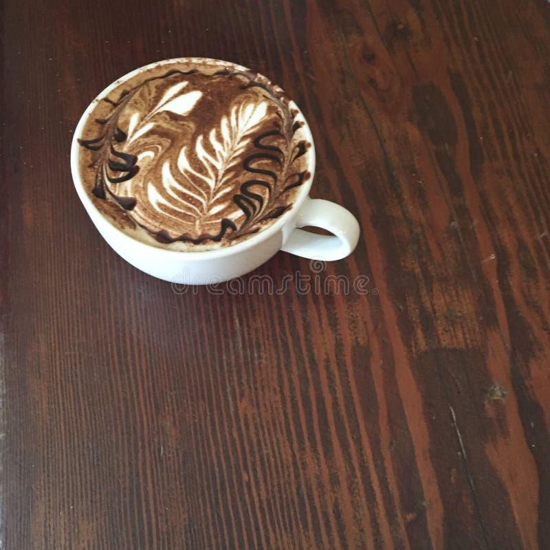 与泡沫艺术和巧克力漩涡的一杯美丽的上等咖啡,在木背景 免版税库存照片