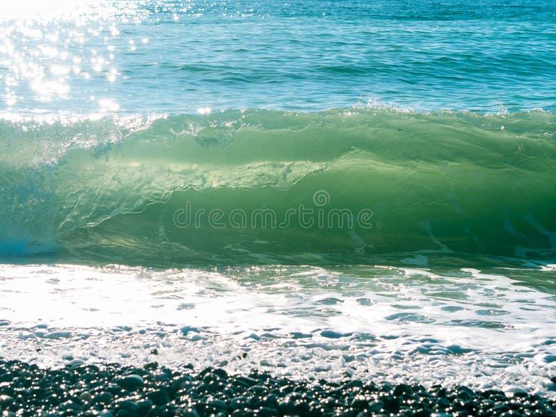 与泡沫,海滩,小卵石,在水的太阳强光的海波浪,黑 库存图片