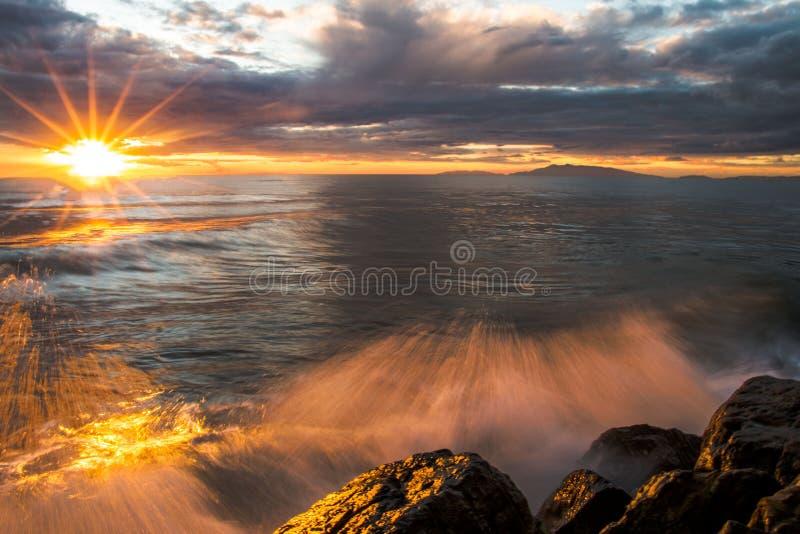 与波浪的日落在岩石 库存图片