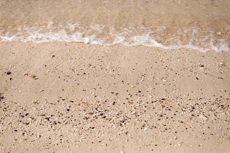 与波浪的沙子海滩 库存照片