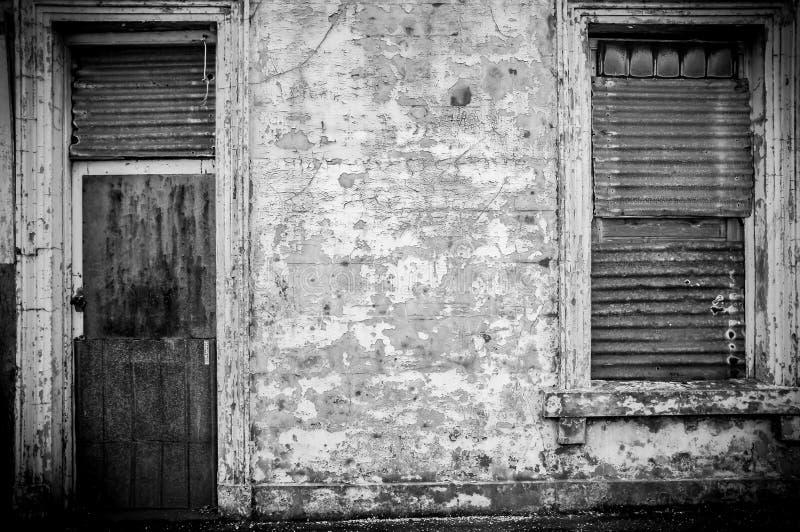 与波状钢门的老被放弃的大厦 免版税库存照片