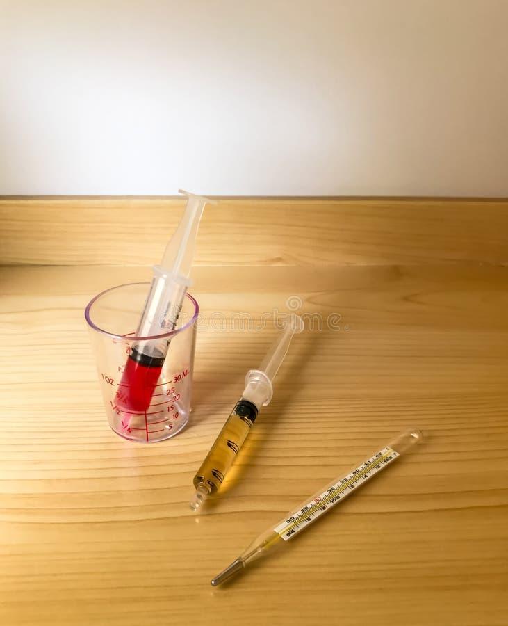 与注射器的药水有流感的孩子的 温度计 免版税库存照片