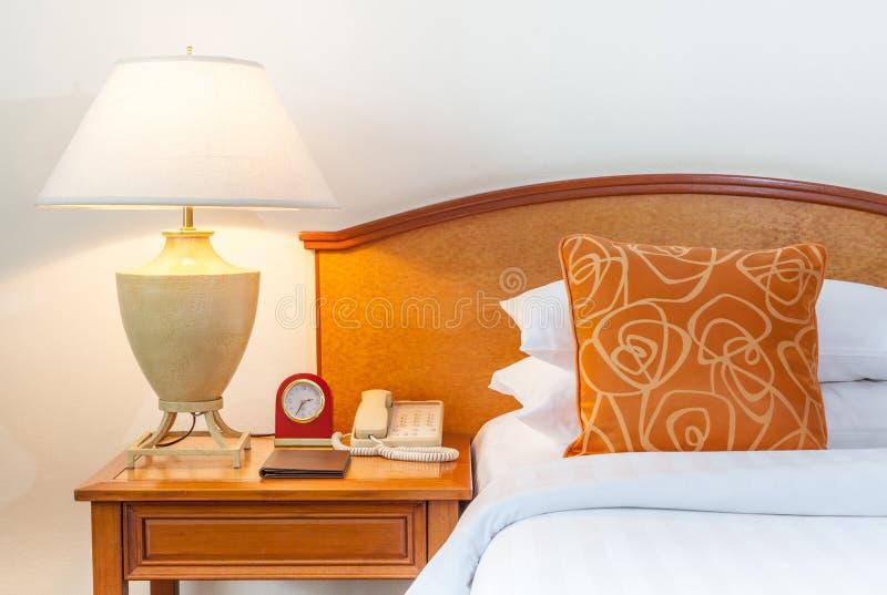 与泰国丝绸枕头,灯,时钟,电话的加长型的床 库存照片