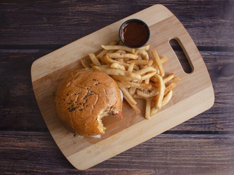 与洋葱圈和辣薯条的自创培根奶酪汉堡 库存图片