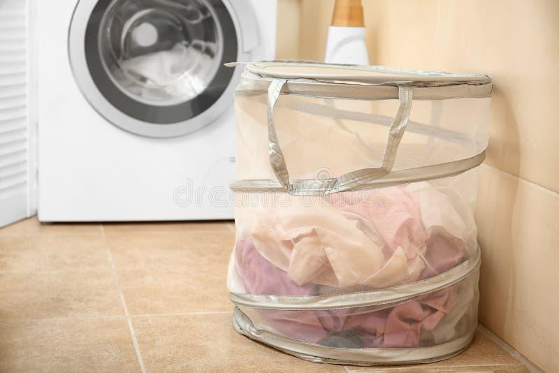 与洗衣店的篮子在洗衣机附近 免版税库存照片
