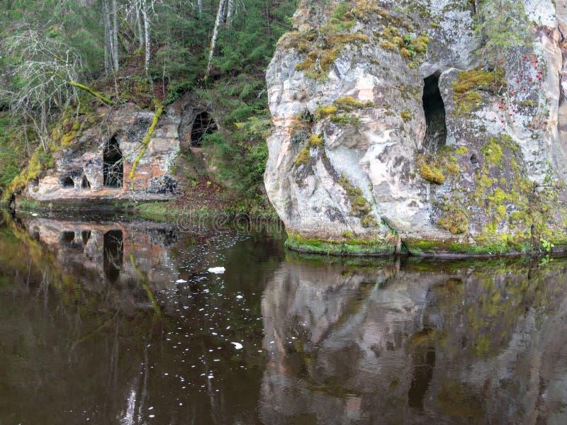 与洞的砂岩岩石在黑暗的水中反射 免版税图库摄影