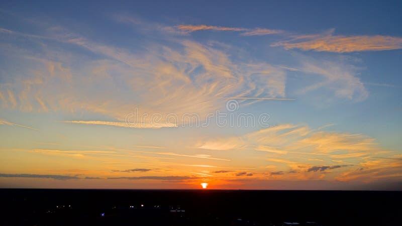 与流动的五颜六色的云彩的日落 免版税库存图片