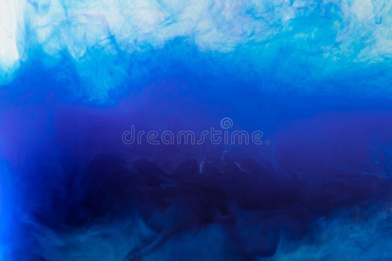 与流动的蓝色发烟性油漆的艺术性的背景在水中 库存图片
