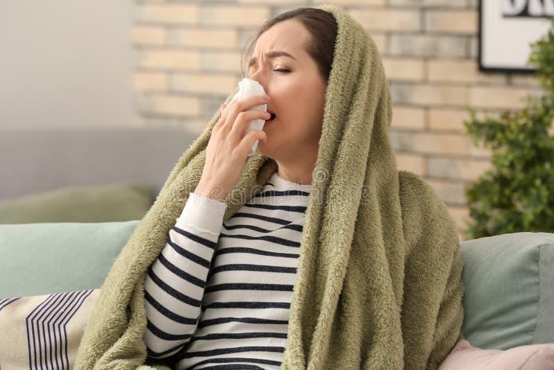 与流感的年轻女人不适在家 库存照片