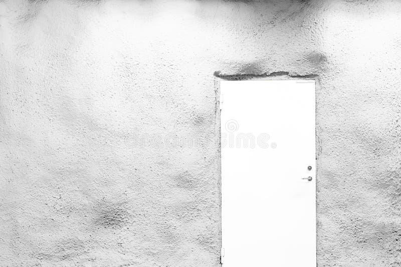 与浅灰色的墙壁的白色门有阴影和光的 库存图片